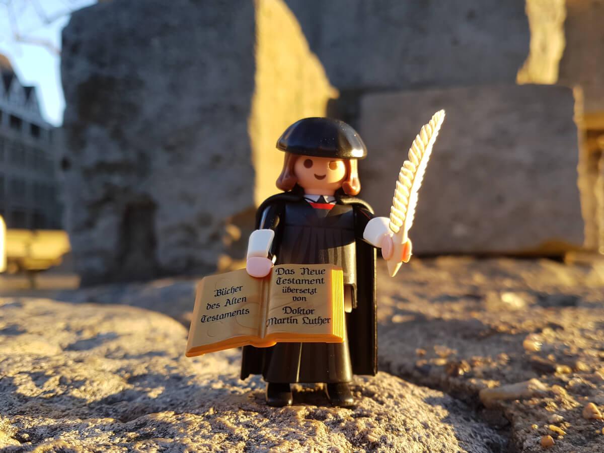 In der rechten Hand hält Martin Luther eine weiße Feder hoch. In der anderen Hand hält die Figur ein aufgeschlagenes Buch.