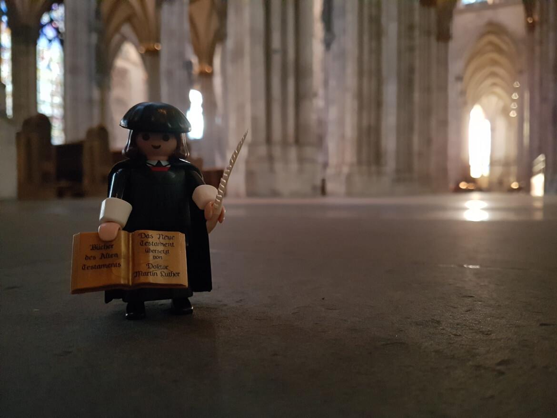Der Playmobil Reformator Martin Luther im Kölner Dom. In den Händen hält er eine Bibel und eine Schreibfeder