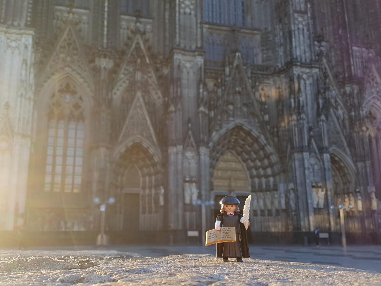 Playmobil Sonderfigur Martin Luther steht vor dem Kölner Dom