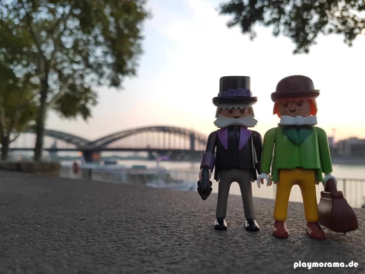 Professor Mobilux und Patrick F. Patrick am Rheinufer in Köln. Im Hintergrund ist die Hohenzollernbrücke zu sehen.