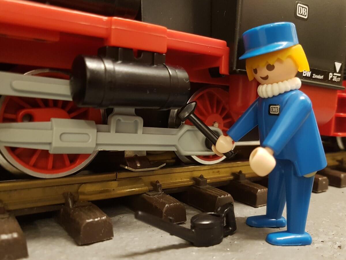 Dampflok Mechaniker mit gelben Haaren und Halskrause.. Er hält einen Hammer in der Hand und arbeitet an der Lok