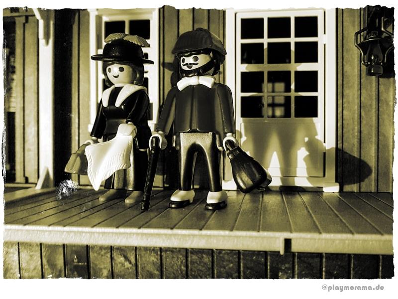 Reisender mit orangefarbenem Hut und orangenen Oberteil & Frau im schwarzen Klein und Hut mit roten Federn 3770. Der Mann und die Western Lady stehen am überdachten Bahnsteig von Colorado Springs