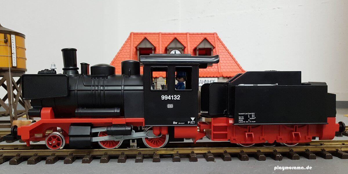 Playmobil Schlepptenderlok steht vor dem Bahnhof. Im Hintergrund sind ein Wasserturm und der Bahnhof zu sehen
