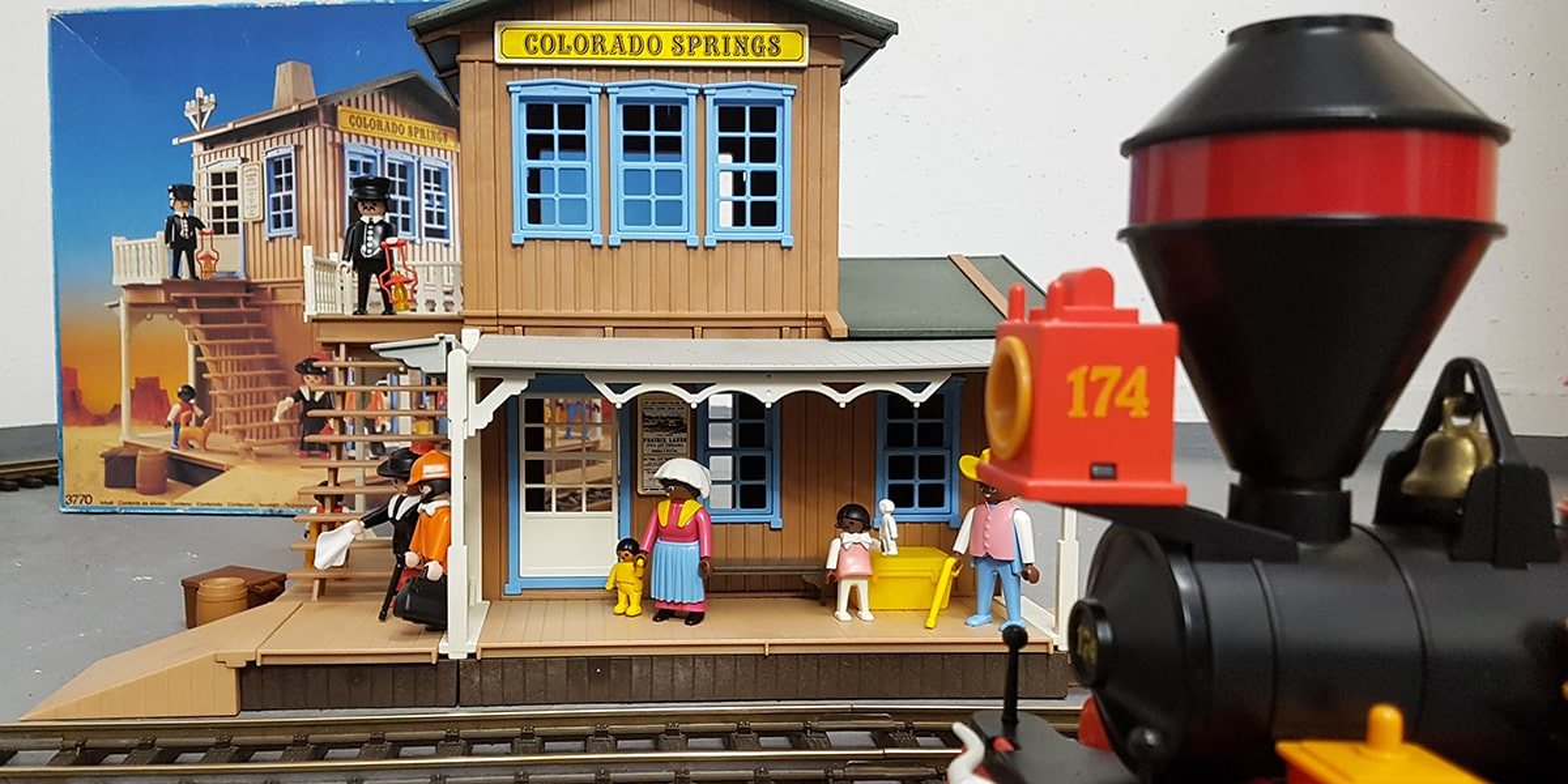 Playmobil Western Station Colorado Springs 3770 aufgebaut mit allen originalen Figuren. Im Hintergrund ist die OPV Originalverpackung des Western Bahnhof zu sehen