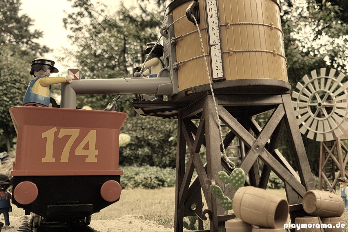 Playmobil Western Lok Steaming Mary wird am Western Wasserturm betrankt.. Im Hintergrund ist das Western-Windrad zu sehen