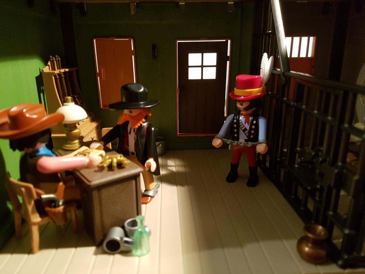 Playmobil Kopfgeldjäger übergibt Bandit an Sheriff. Der Sheriff freut sich über einen neuen Übernachtungsgast