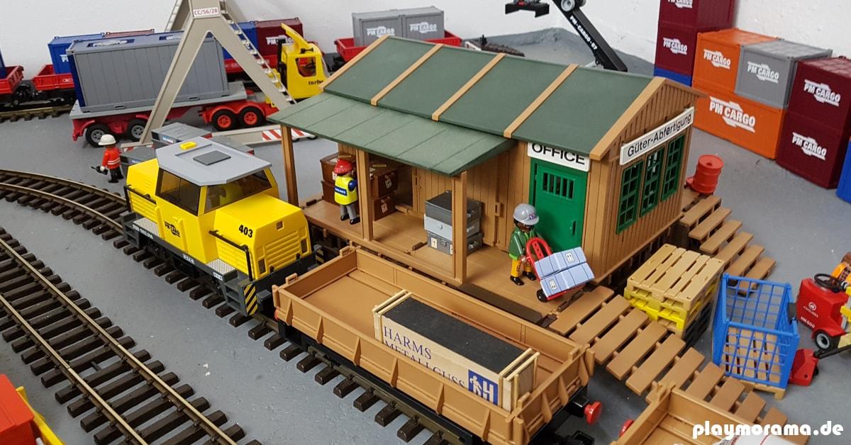 Playmobil Güterabfertigung 4305-A. Ein schönes Gebäude von der Playmobil-Eisenbahn. Im Hintergrund ist ein Containerterminal zu sehen