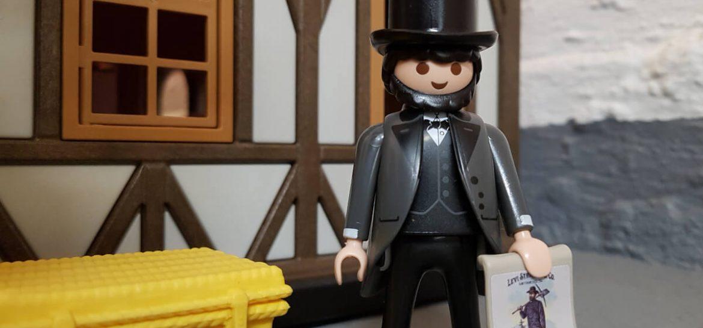 Playmobil Levi Strauss steht vor einem Fachwerkhaus