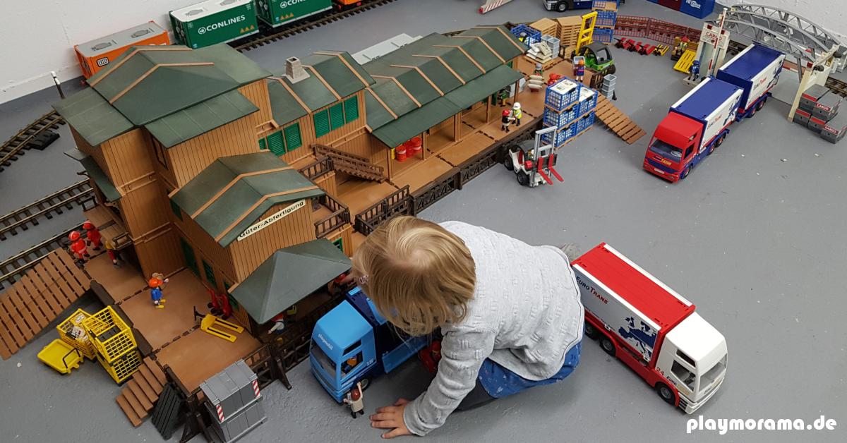 Kind spielt mit der Playmobil Güterabfertigung