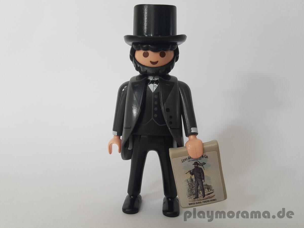 In der Hand hält die Playmobil Figur von Levi Strauss einen Abdruck eines Werbeplakates aus der Anfangszeit der Jeans.