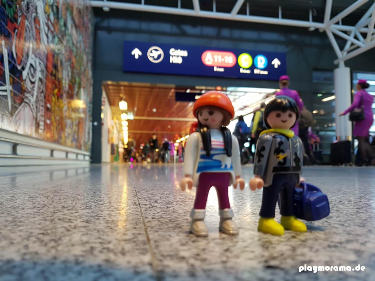 Playmobil Touristen nach Ankunft in Island am Internationalen Flughafen in Keflavik. Im Hintergrund sind Stewardessen von WOW-Air zu sehen.