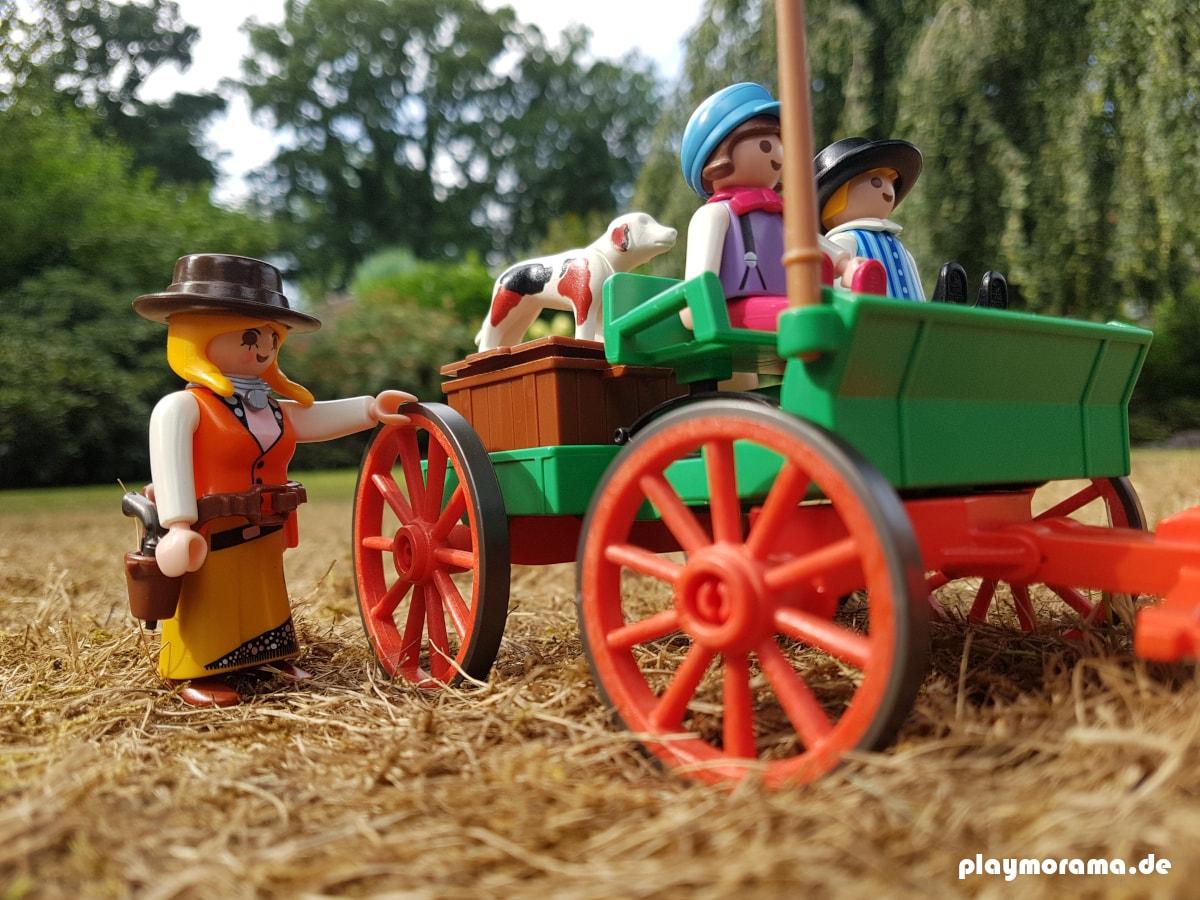 Die Kinder warten mit dem Hund auf dem Farmwagen, während Anni die Säcke aufläd