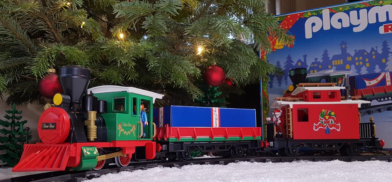 Festlicher Playmobil Weihnachtszug vor dem Tannenbaum. Im Hintergrund ist die OVP zu sehen