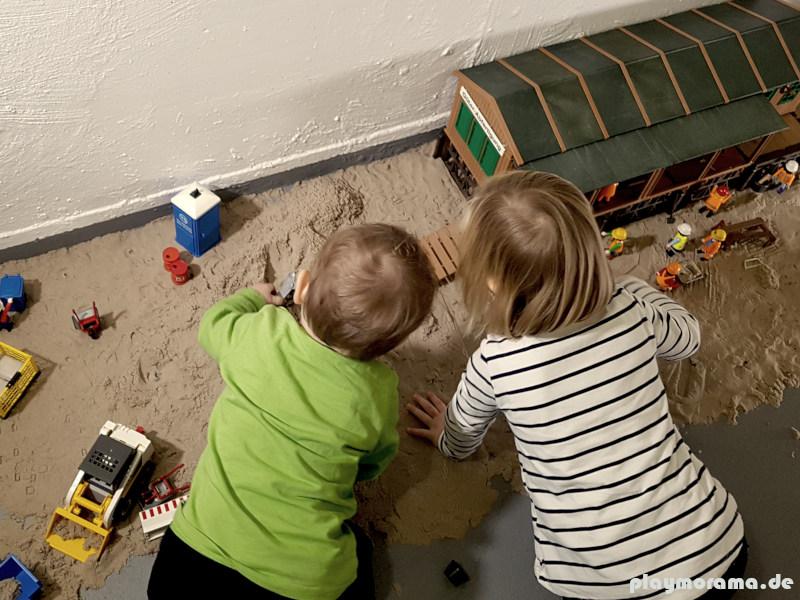 Die Kinder spiel mit Bagger, Radlader und Figuren auf der Baustelle