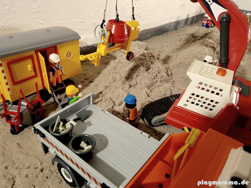 Der Kettenbagger 5282 hebt den von Baustellen LKW gelieferten Zementmischer von der Ladefläche