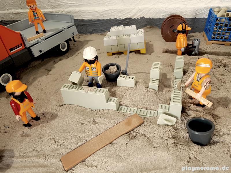 Playmobil Arbeiter mauern eine Mauer für das Fundament.