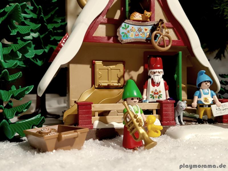 Der Weihnachtsmann mit seinen Heldern vor der Weihnachtsbäckerei mit Plätzchenformen